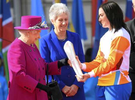 Retired cyclist Anna Meares, right, receives the Commonwealth Games relay baton from Britain's Queen Elizabeth II, left,  at the launch of the relay at Buckingham Palace in  London on Monday.  The XXI Commonwealth Games are  being held on the Gold Coast in Australia in 2018.