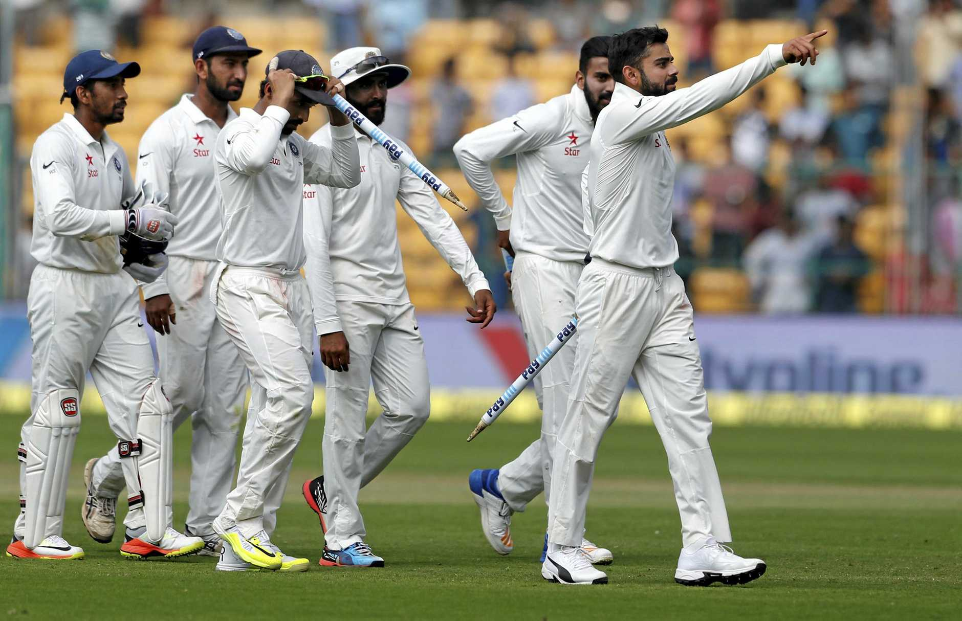 India's captain Virat Kohli, right, leads his teammates off the field after their win over Australia on the fourth day of their second test cricket match in Bangalore, India, Tuesday, March 7, 2017. Indian won the match by 75 runs. (AP Photo/Aijaz Rahi)