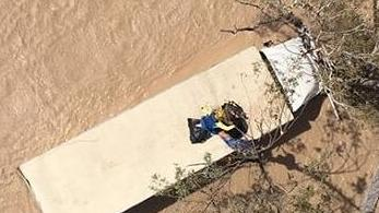 A truck driver has been rescued from the top of his vehicle, which was stuck in floodwaters near Miles. Picture: RACQ LifeFlight Rescue