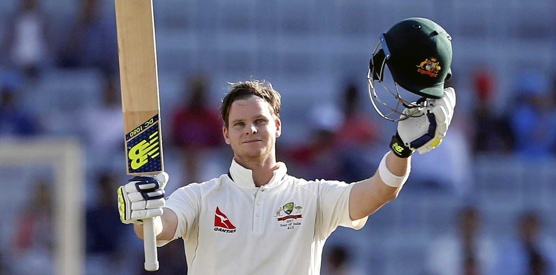 Australia's captain Steven Smith raises his bat and helmet to celebrate scoring a century against India in Ranchi