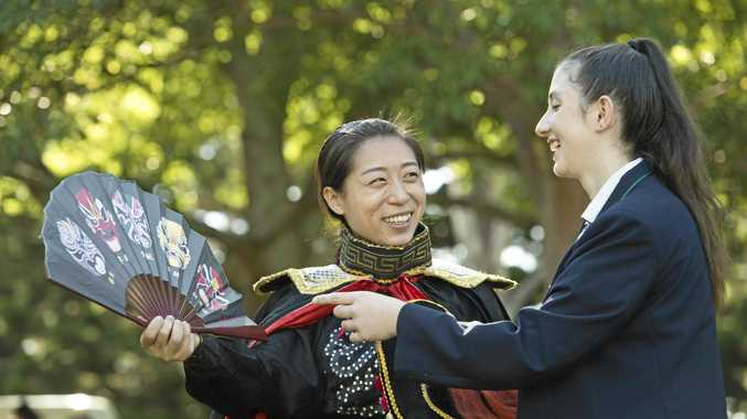 CULTURAL EXCHANGE: Peng Zhen Zhen of Wuqiao Acrobatic Troupe shows of her traditional costume to St Ursula's College student Tiffany Dennis at the UNESCO Ambassadors welcome breakfast on Harmony Day.