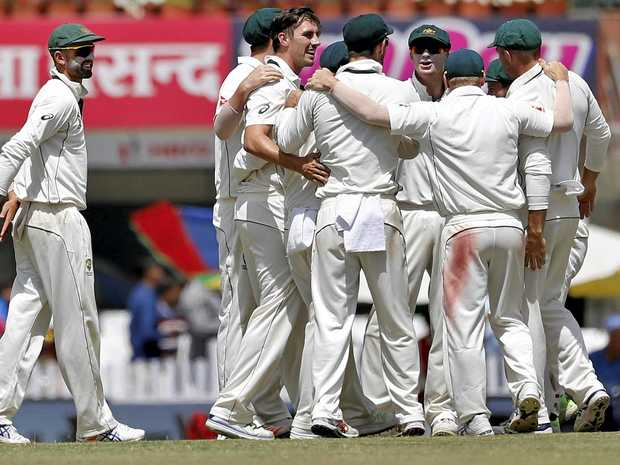Australian fast bowler Pat Cummins, without cap, celebrates with teammates after the dismissal of India's captain Virat Kohli during the third day of the third Test in Ranchi.