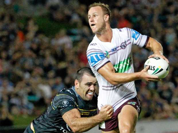 Manly skipper Daly Cherry-Evans looks to offload as Cowboys defender Kane Linnett grabs hold.