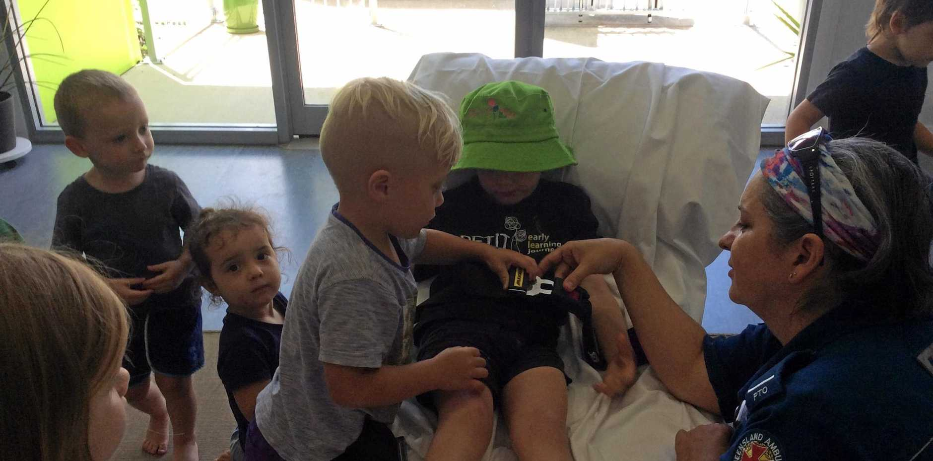 CALMING FEARS: Petit Early Learning Journey - Marian children help each other into the stretcher when the Mackay ambulance came to visit.