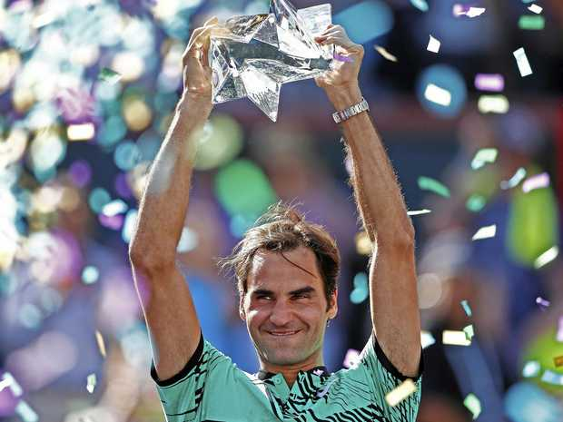 Roger Federer of Switzerland holds the trophy after winning the final against Stan Wawrinka of the BNP Paribas Open tennis tournament at the Indian Wells Tennis Garden.