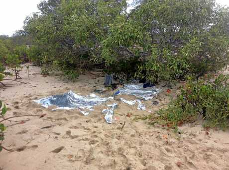 The scene of a helicopter crash on Curtis Island, where two men were lucky to survive after they were found more than a day after the crash. The men were found with these items on a beach, away from the mud flats where the chopper crashed.
