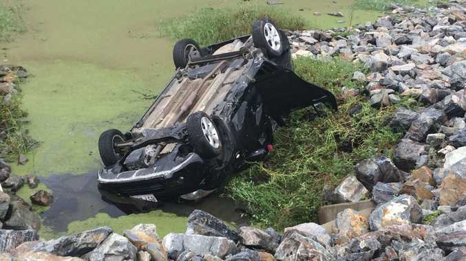 ROLLOVER: Car rolls off bridge into a lagoon.