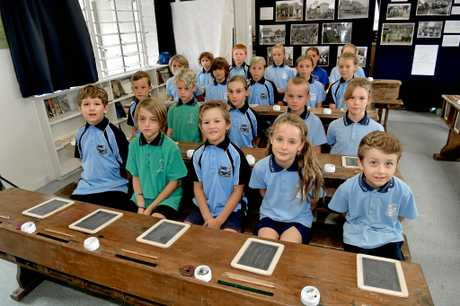 Coolum State School celebrates 100 years with a century old classroom.Jann Victor with students in the old classroom.