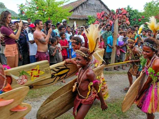 VILLAGE children carry locally made timber surfboards during the opening ceremony of the WSL Kumul PNG World Longboard Championships.
