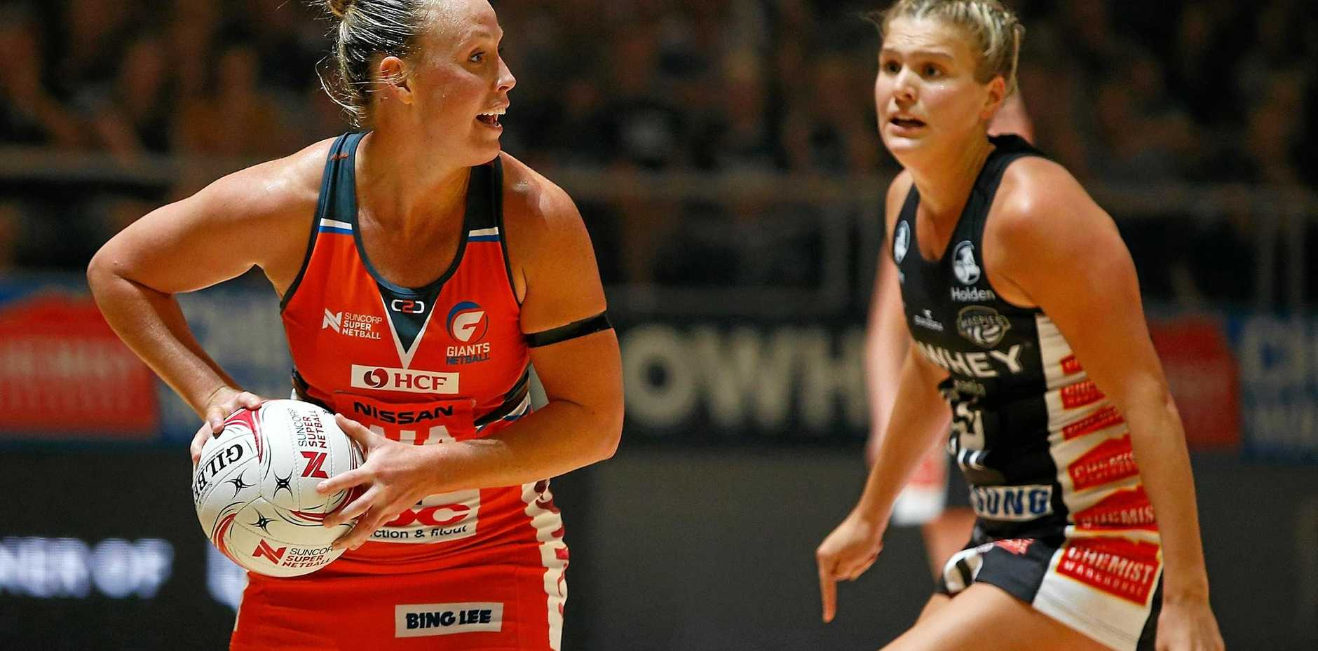 Kim Green (left) of the Giants looks to make a pass during the round three Super Netball match against the Magpies.