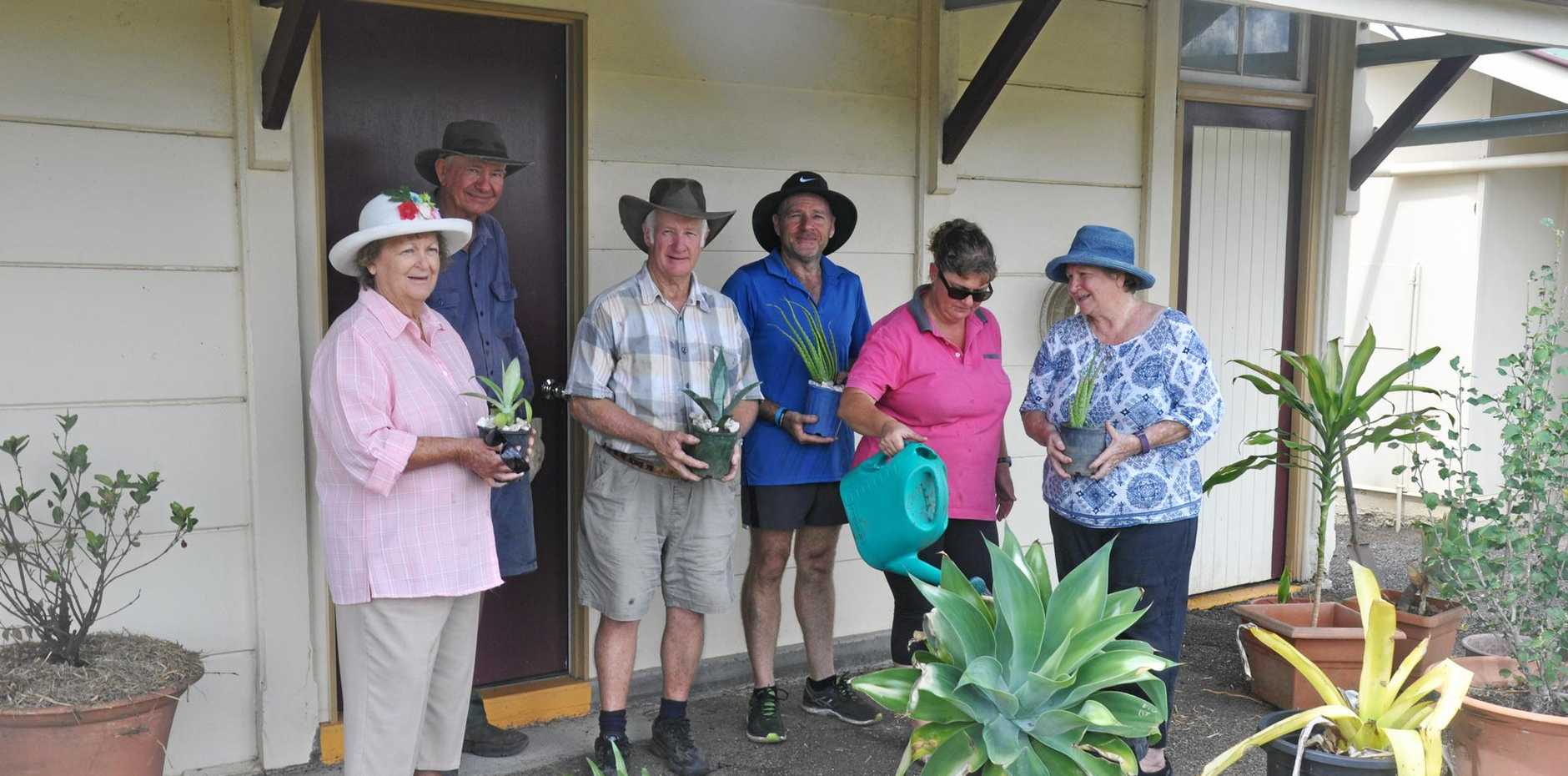 GREEN THUMB: Volunteers work to beautify the old Monto railhouse with a garden.