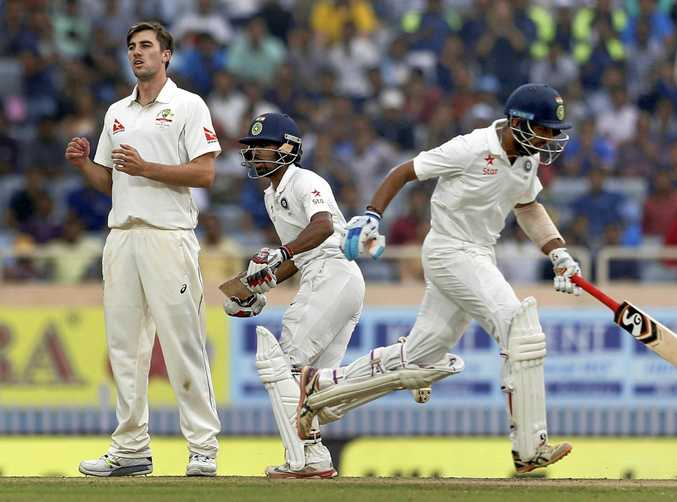 Australia's Pat Cummins (left) watches as India's Wriddhiman Saha (centre) and Cheteshwar Pujara run between the wickets during the fourth day of the third Test in Ranchi.