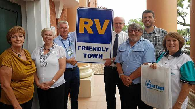 Nancy Bates, Cr Anne Maddern, Richard Mainey, Cr Chris Loft, Darryl Stewart, Nan Ott and Cr Paul Truscott with the sign declaring Maryborough an RV friendly town.