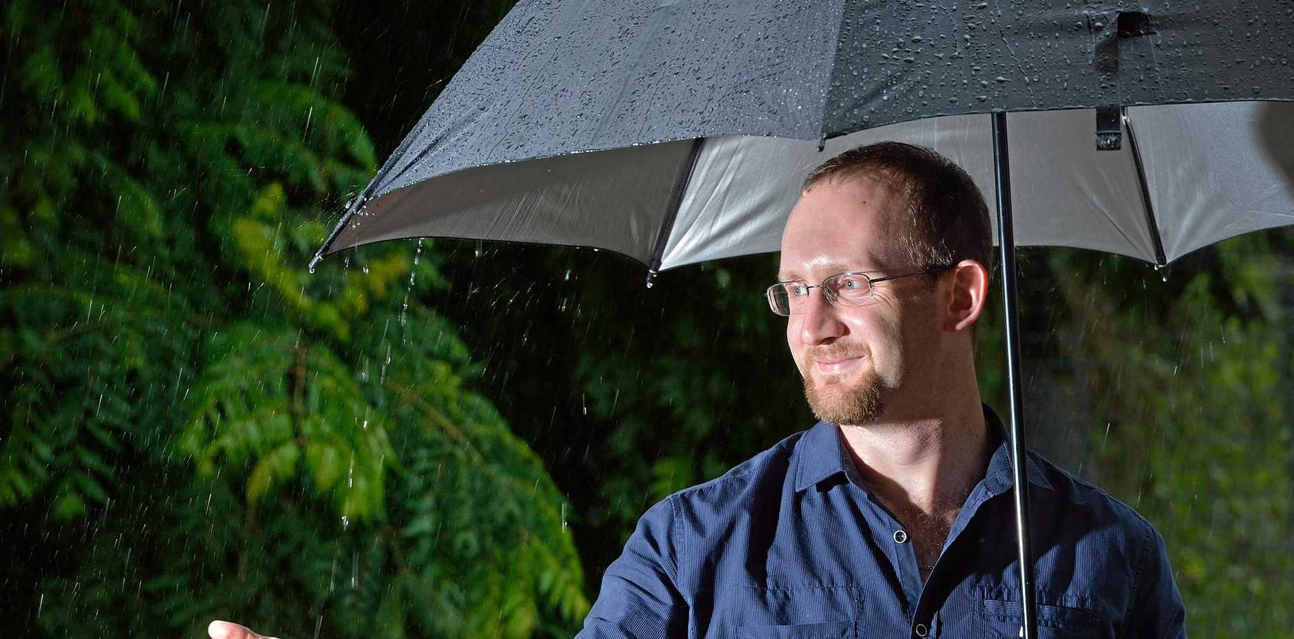 SMILIN' IN THE RAIN: Scott Kovacevic enjoys the rain in Gympie yesterday, with more expected as a low pressure system develops in the Coral Sea.