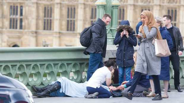 Is this woman really indifferent to the tragic scene unfolding next to her or is she simply walking past quietly like hundreds of others did? Picture: REX/Shutterstock/australscope
