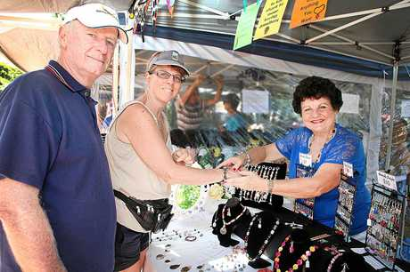 Debbie Hall, supported by husband Steve, tries on a braclet at Evelyn Willebrands' stall at the Pier Park Community Markets on Saturday. The Sydney couple are visiting Hervey Bay to attend a wedding. Photo: Jocelyn Watts / Fraser Coast Chronicle
