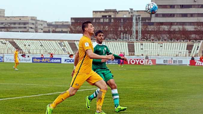 Iraq's Mohanad Abdulraheem (right) battles for the ball with Australia's Tomi Juric.