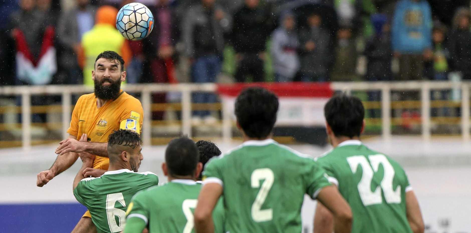 Australia's Mile Jedinak heads the ball against Iraq during their World Cup qualifier in Tehran.