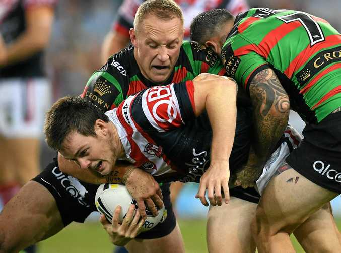 Luke Keary of the Roosters is tackled by Jason Clark (left) and Adam Reynolds of the Rabbitohs.