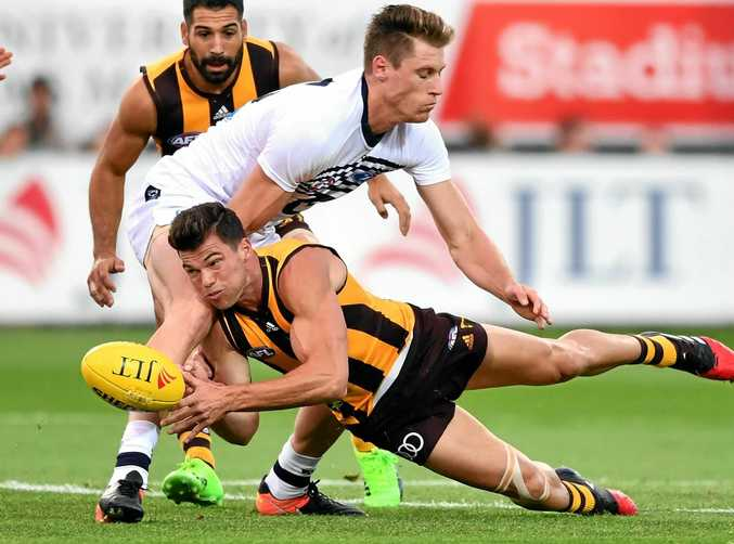 Jaeger O'Meara of the Hawks handballs while being tackled by Mark Blicavs of the Cats during the 2017 JLT Community Series.