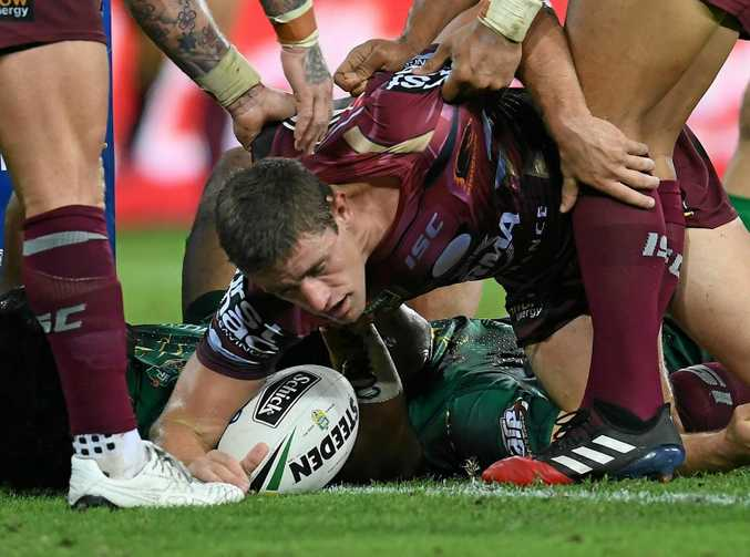 Andrew McCullough of the Brisbane Broncos is lifted by his teammates after scoring a try against the Canberra Raiders.