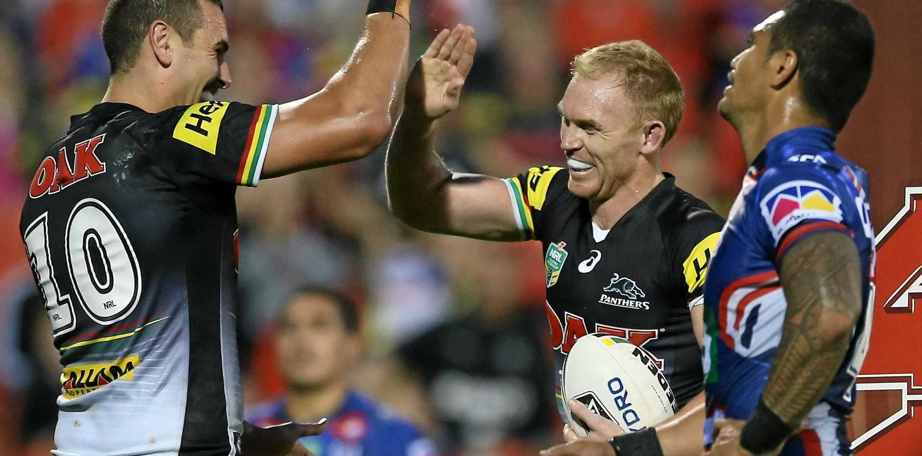 Peter Wallace of the Panthers celebrates with Reagen Campbell-Gillard after scoring against the Newcastle Knights.