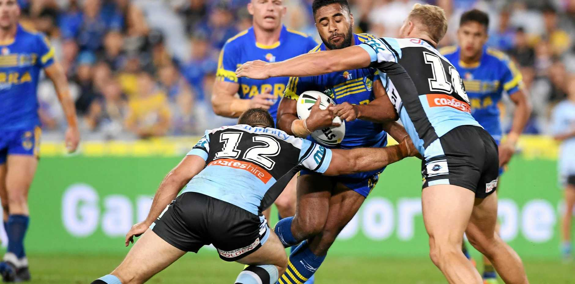 Michael Jennings (centre) of the Eels is tackled by Matt Prior (right) and Wade Graham of the Sharks.