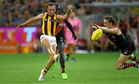 Billy Hartung of the Hawks (left) gets boot to ball.