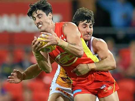 Alex Sexton of the Gold Coast Suns (left) is tackled by Sam Mayes of the Brisbane Lions.