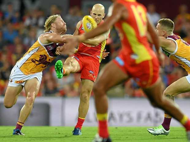 Gary Ablett of the Gold Coast Suns (centre) is tackled by Daniel Rich of the Brisbane Lions.