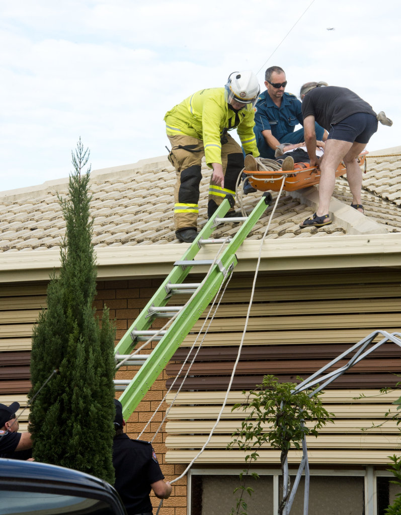QFES retrieve man from roof of house in Sampson St Wilsonton. Sunday Mar 26, 2017.