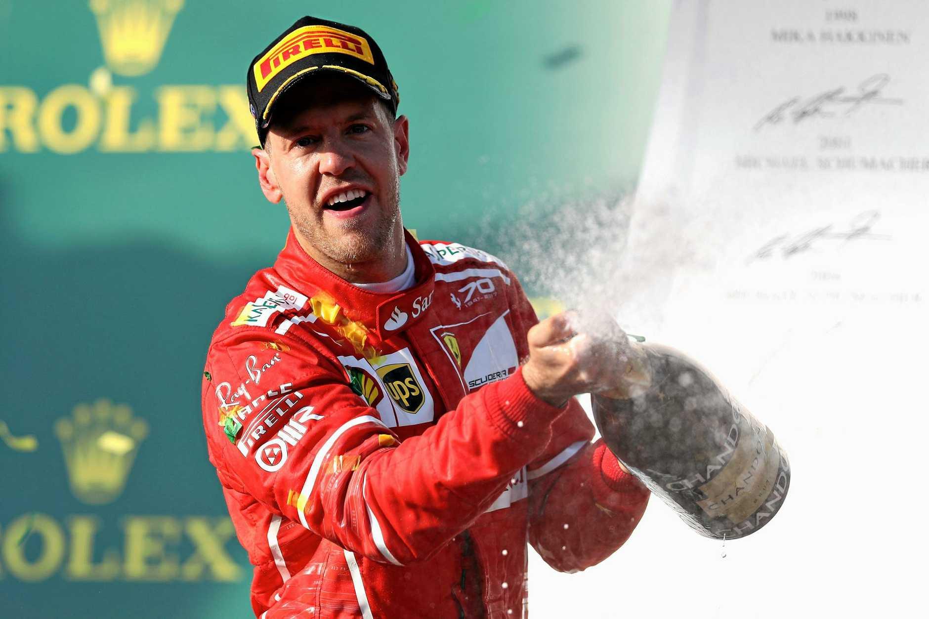 WINNER: Sebastian Vettel celebrates his victory on the podium.