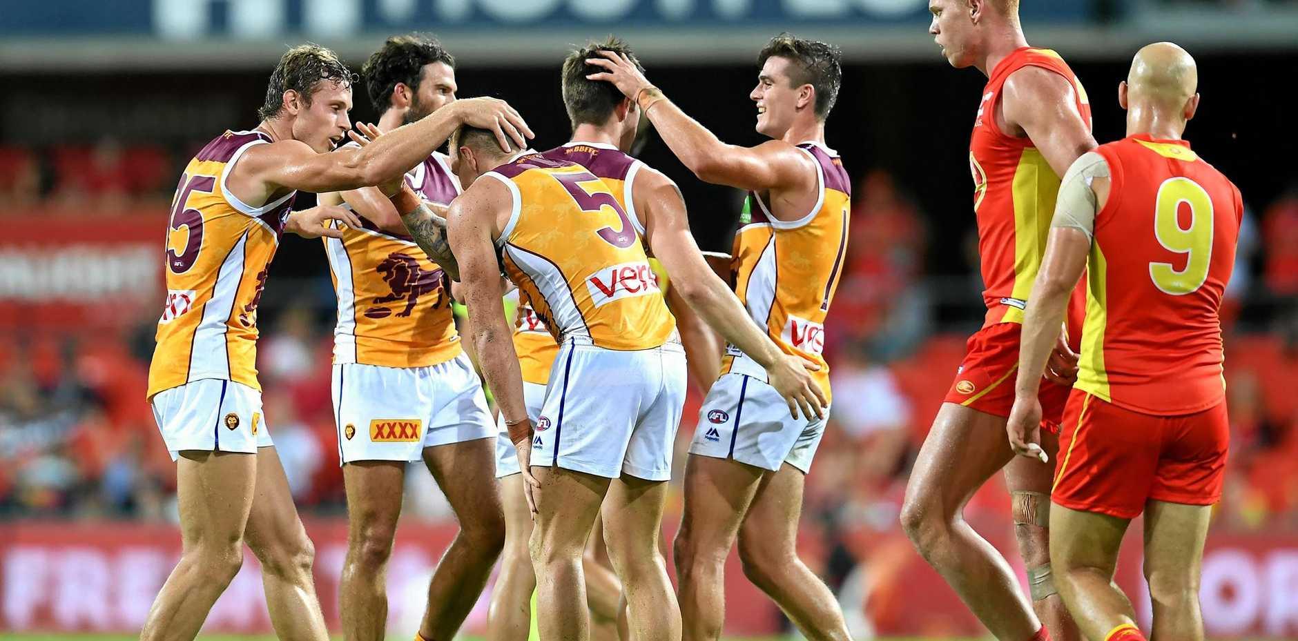 Brisbane Lions players celebrate scoring a goal