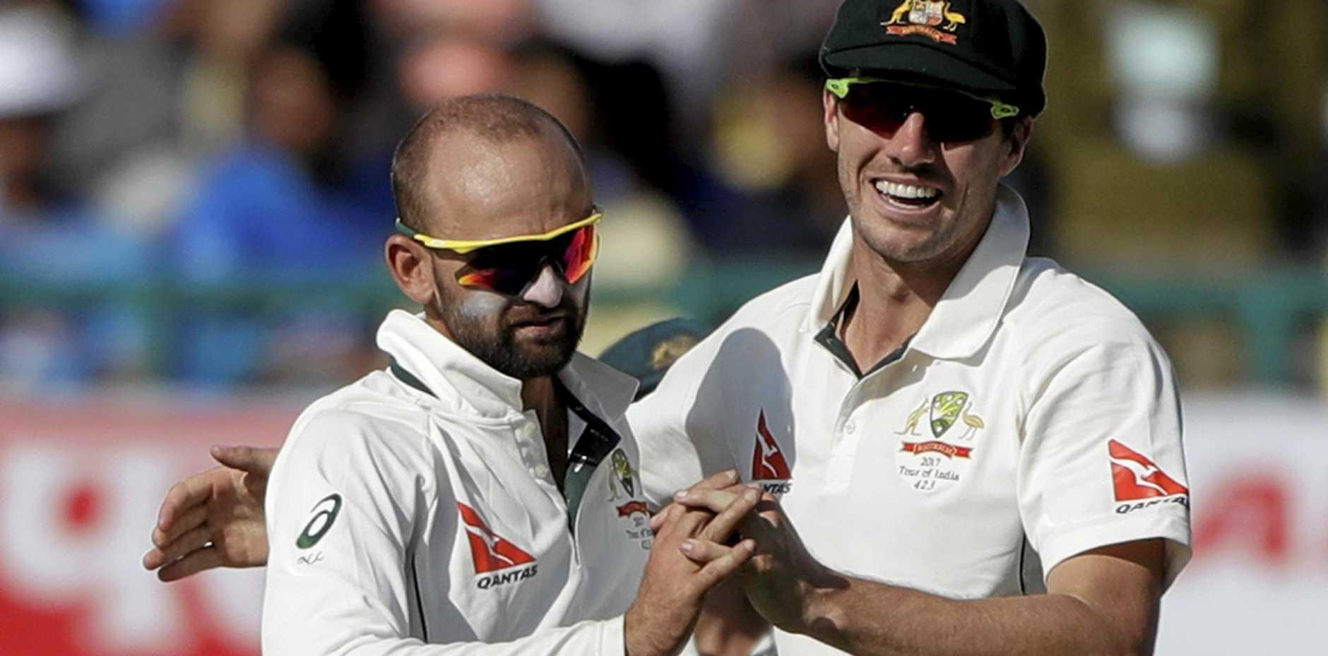 Australia's Nathan Lyon, left, and Pat Cummins celebrate the dismissal of India's Ravichandran Ashwin