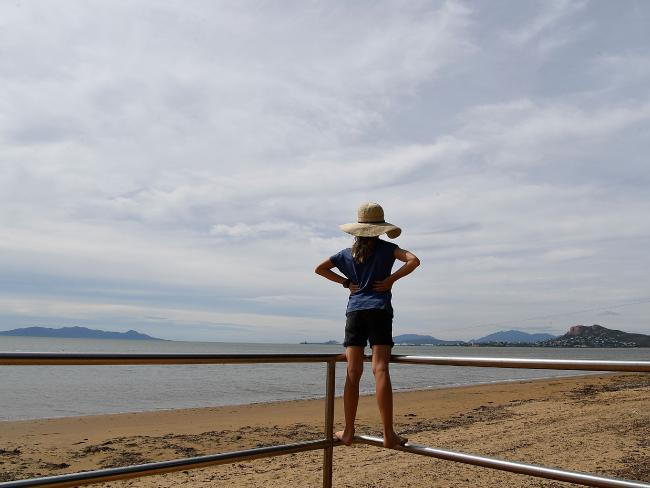 A young girl looks out to sea in Townsville as residents prepare and wait for Cyclone Debbie to arrive. Picture: Ian Hitchcock
