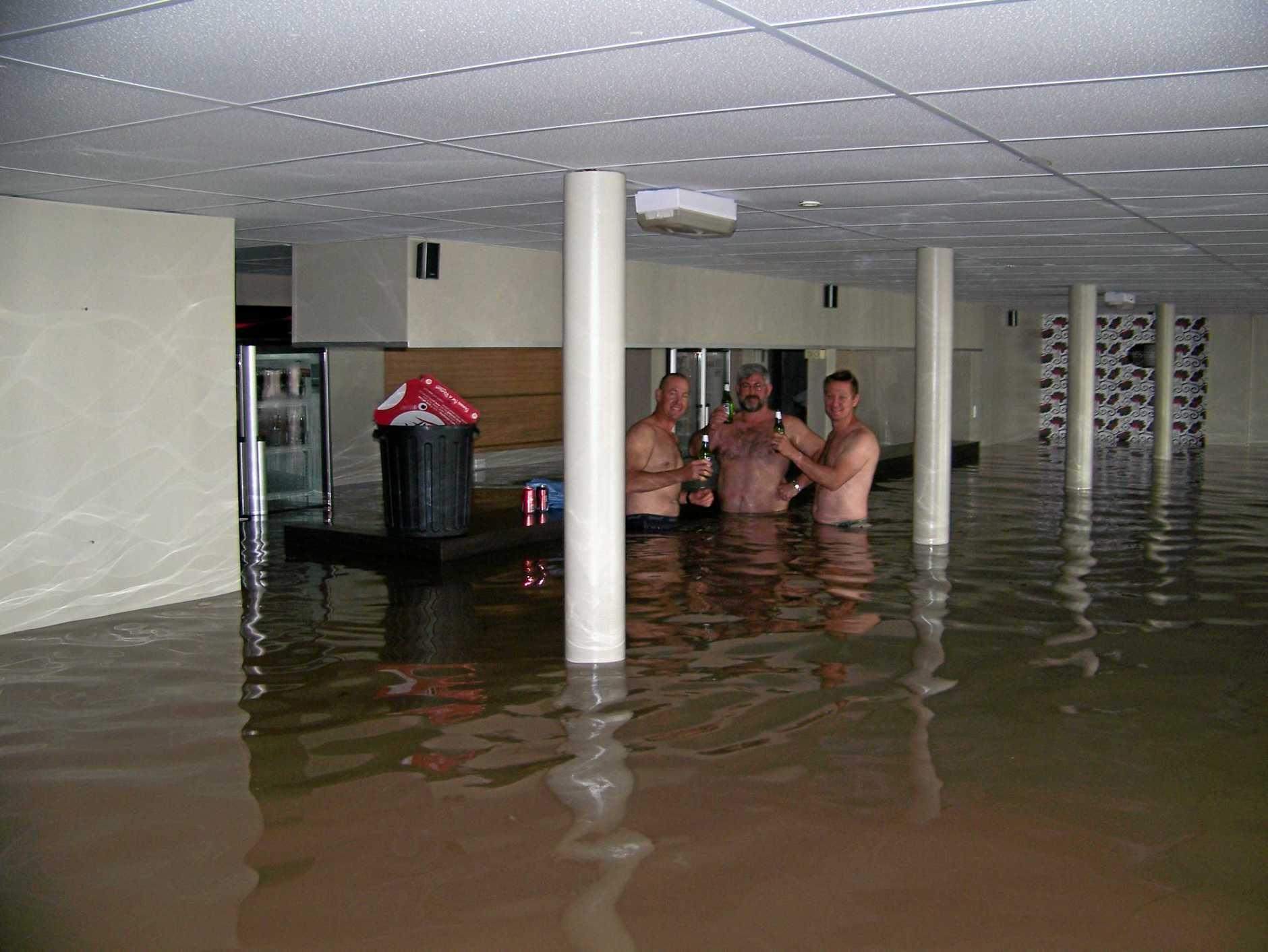 FLOOD BAR BORN: Nigel Jensen, Bruce Dalton and Brett Jensen share a beer at the Spinnaker Bar and Restaurant during the floods.