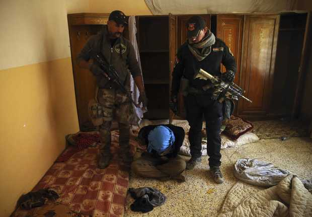 Iraqi special forces soldiers stand guard over an alleged Islamic State group collaborator, inside a house in the Al-Samah front line neighborhood, in Mosul, Iraq, Wednesday, Nov. 23, 2016.