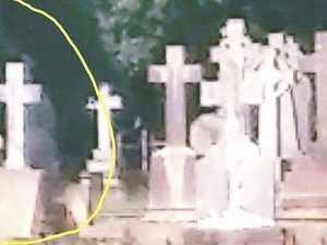 Creepy 'ghost' photographed standing behind grave