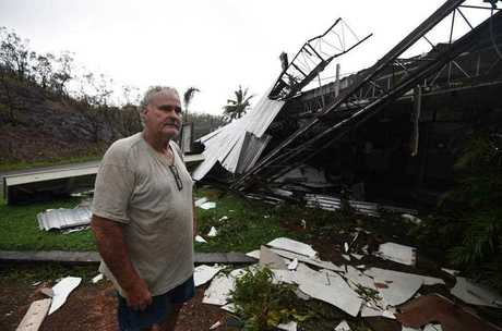 Dave Mcinnerney inspects the damage to his motel at Shute Harbour, Airlie Beach on Wednesday (AAP Image/Dan Peled)
