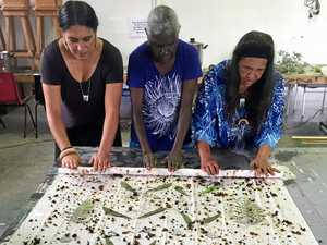 Fibre and textile artist, Kylie Caldwell, and coordinator of The Casino Wake Up Time Group rolls up a silk print with Bundjalung and Kunwinjku artists taking part in cultural exchange in Northern Rivers.