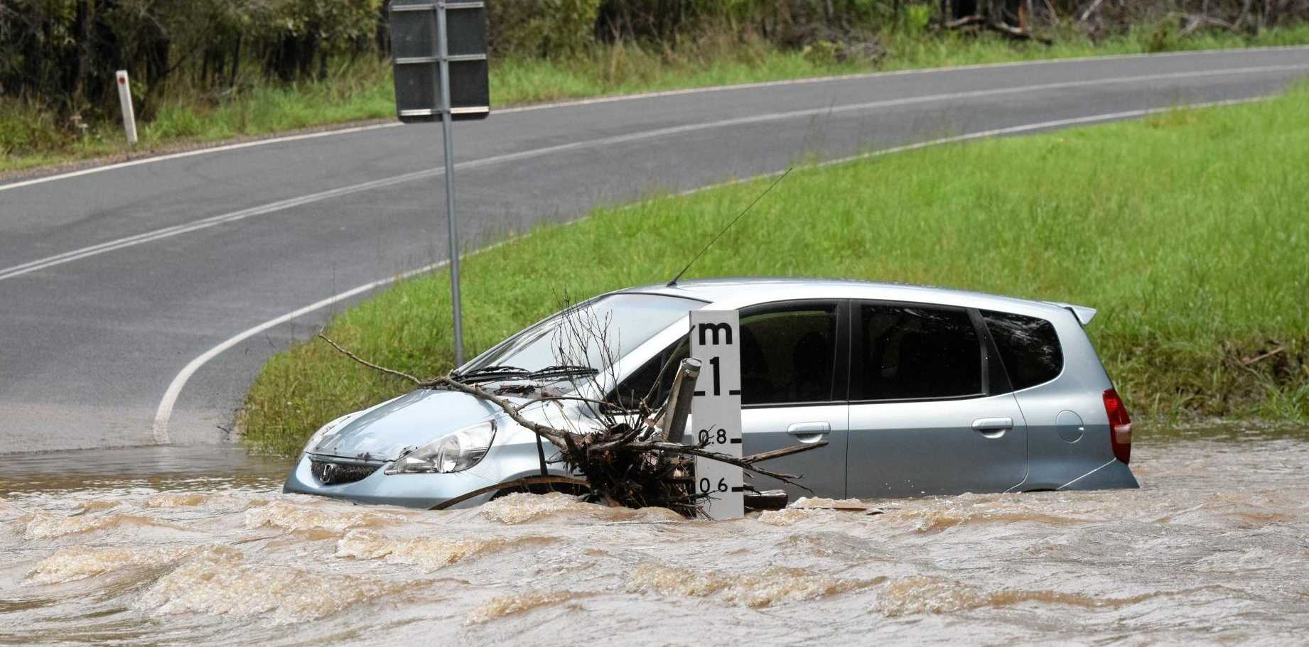 FORGET IT: Police are warning drivers not to risk driving across flooded roads after a man had to flee his vehicle on a crossing on Booyan Rd, Moore Park, on Wednesday, March 29, 2017.
