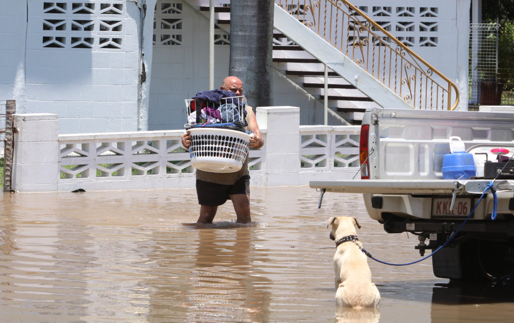 Andrew Baker was on hand to help his children move their possessions from their Bolsover Home as Fitzroy River flood waters already spill into low lying parts of Depot Hill, Rockhampton. Andrew's dog Dozer watches on. Photo Chris Ison / The Morning Bulletin ROK311210-flood-c11