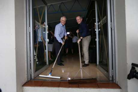 Australian PM Malcolm Turnbull (L) and Opposition Leader Bill Shorten sweep water from a store in a cyclone damaged area March 30, 2017 in Bowen, Australia.