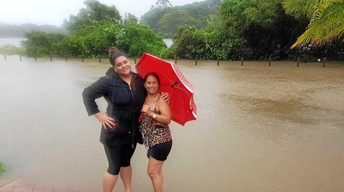 Tumbulgum residents Rachel Borey and Josephina McLean watch floodwaters rise on Riverside Drive ahead of a king tide on Thursday.