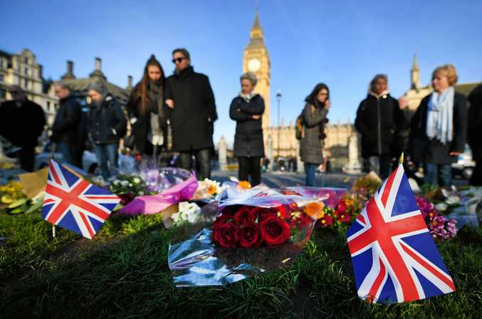 ATTACKED: People stop to pay their respects at the site of the terror attack on Westminster Bridge.