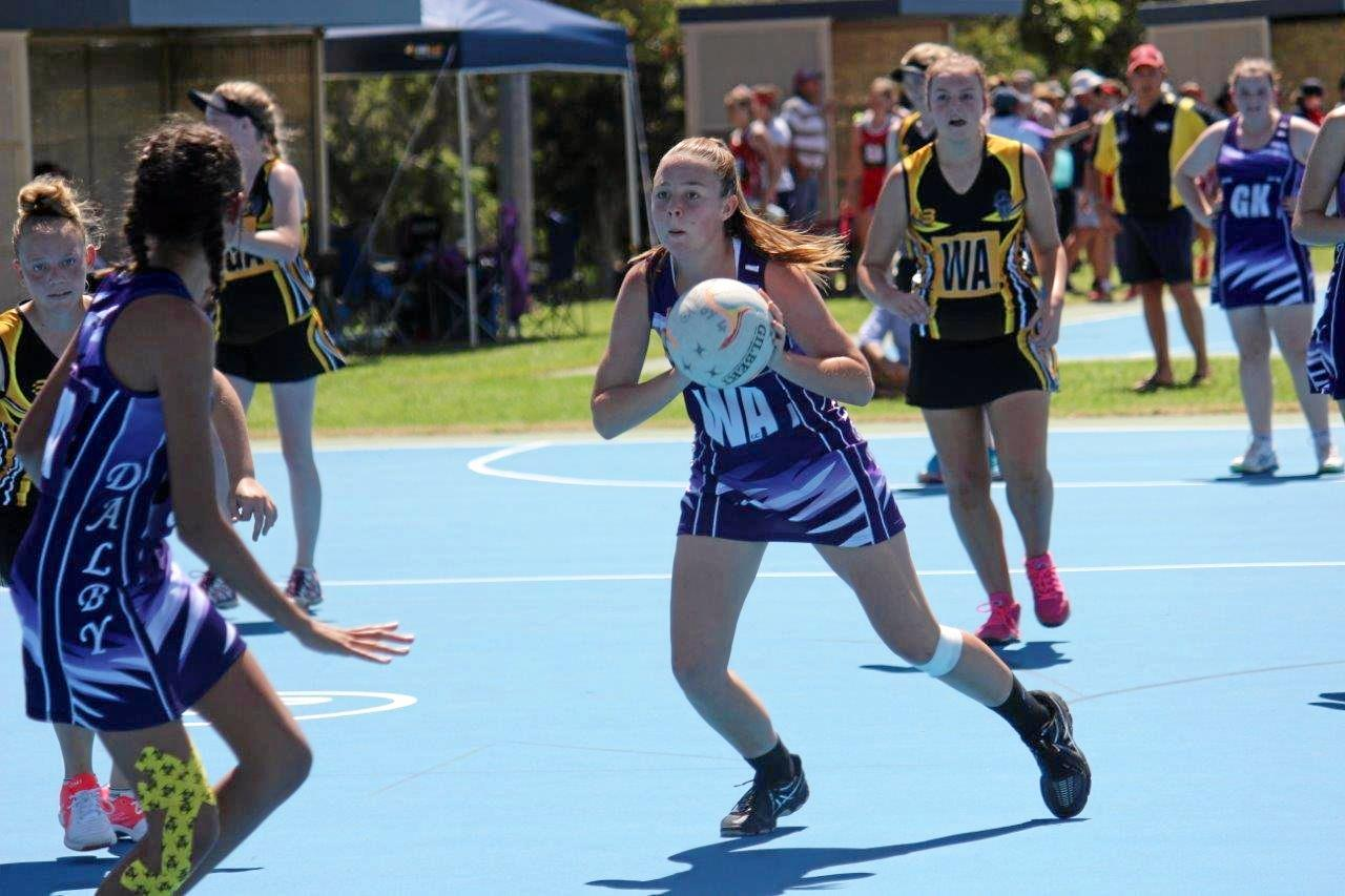 QUICK PASS: Gabby Parker of the under-15 and -16 team passing the ball to team mate Jasmine Houlder.