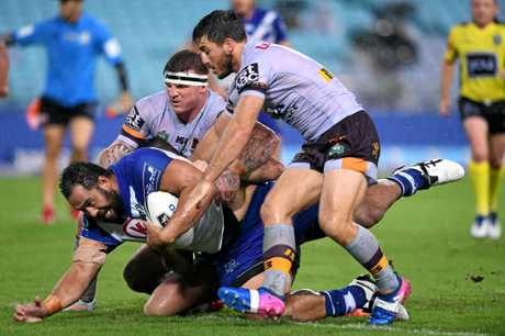 Sam Kasiano (left) of the Bulldogs is tackled by Josh McGuire (centre), Ben Hunt (right) and Matthew Gillett of the Broncos