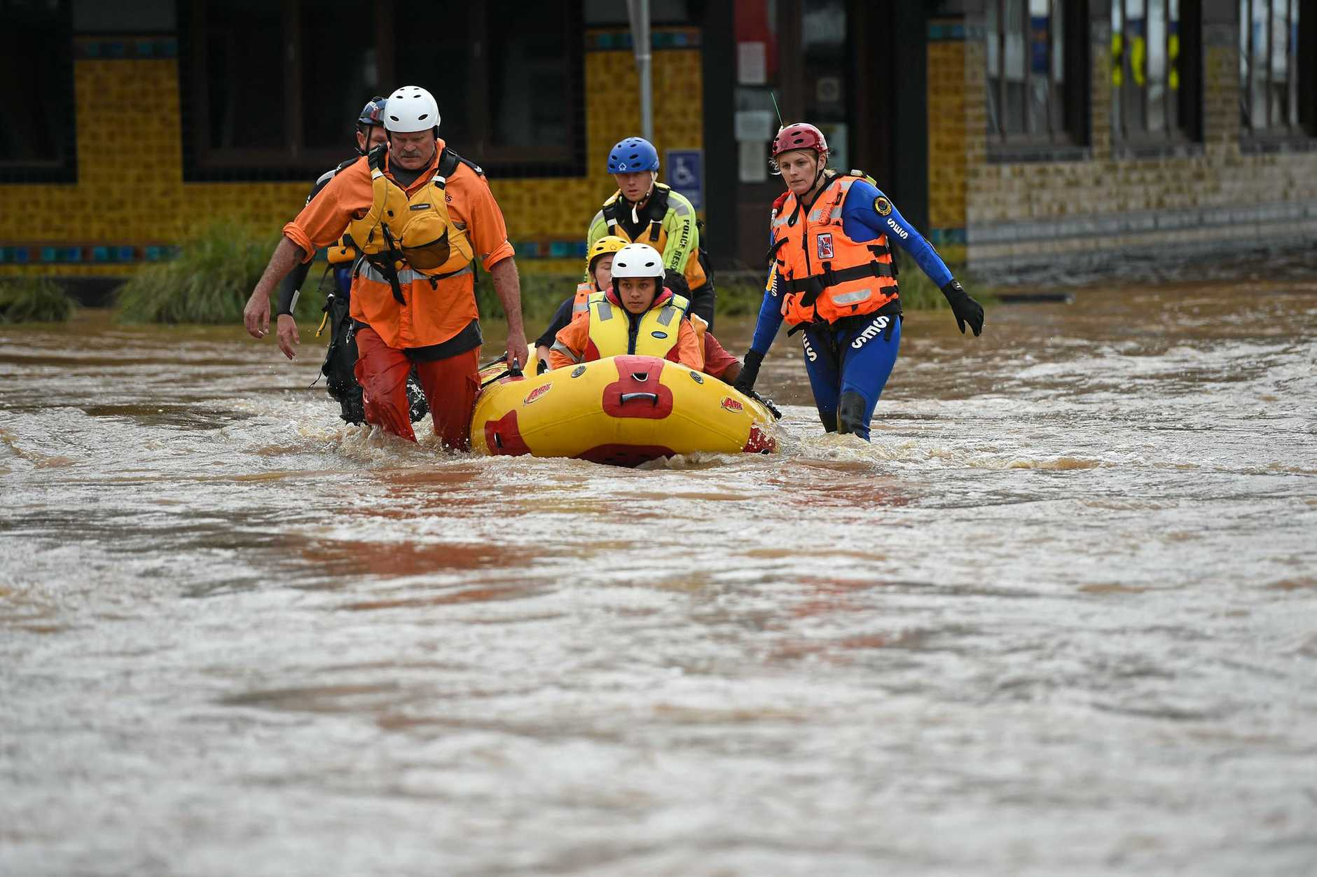Emergency services escort a man they rescued to saftey after flooding hit the centre of Lismore.