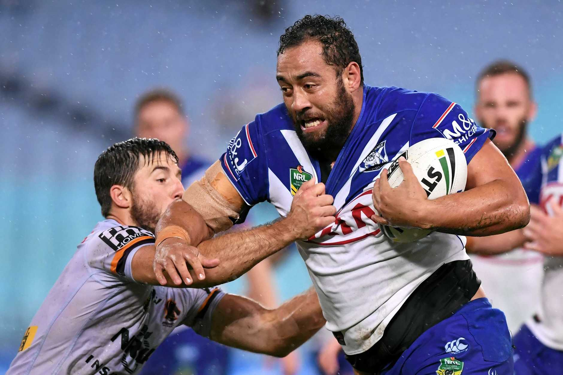 Sam Kasiano (right) of the Bulldogs is tackled by Ben Hunt of the Broncos.