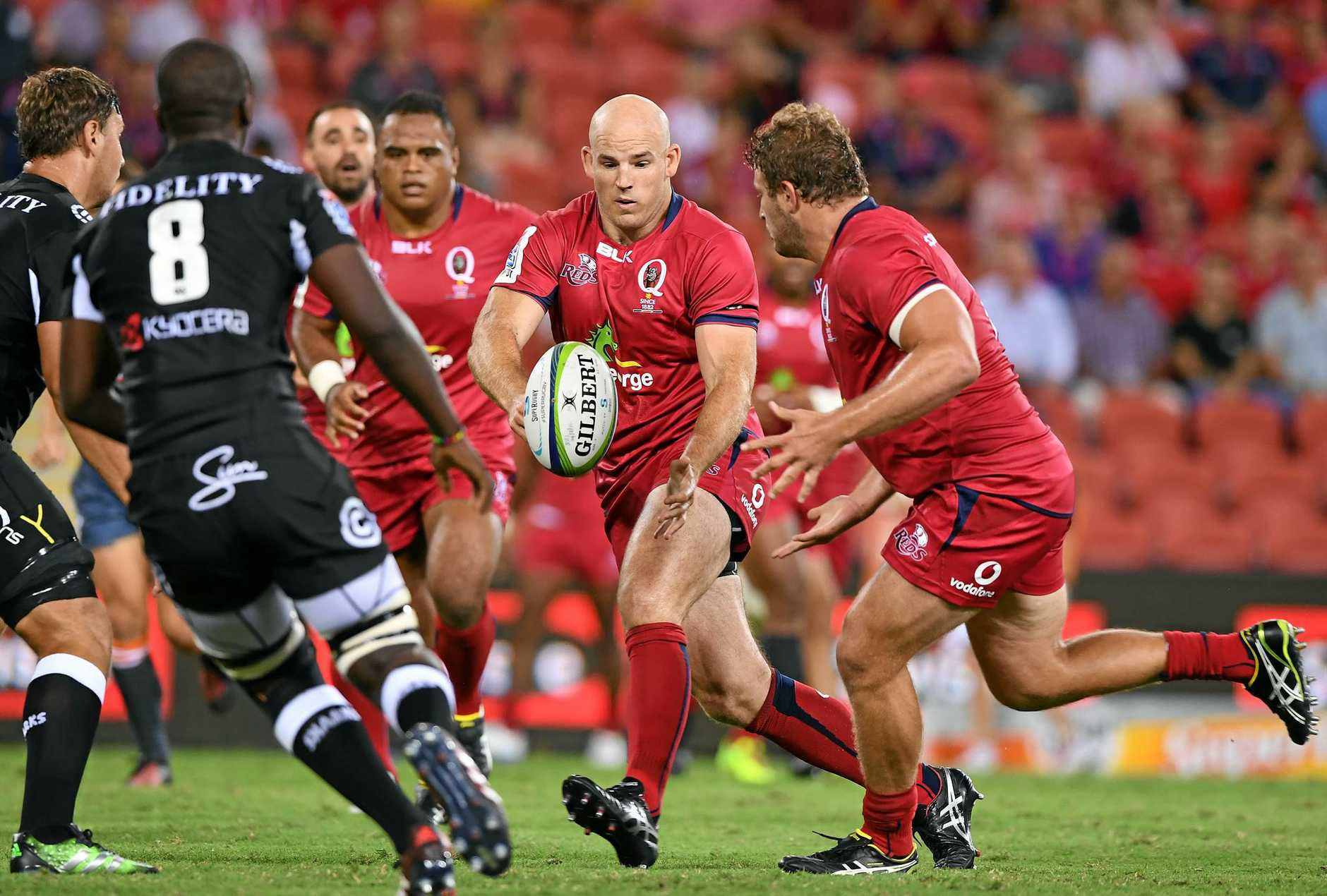 Reds player Stephen Moore passes to James Slipper in round one of Super Rugby against the Sharks.